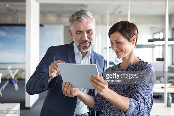 businessman and businesswoman with tablet in office - arbeitskollege stock-fotos und bilder