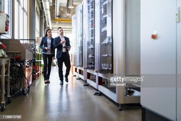businessman and businesswoman with tablet walking and talking in a factory - formelle geschäftskleidung stock-fotos und bilder