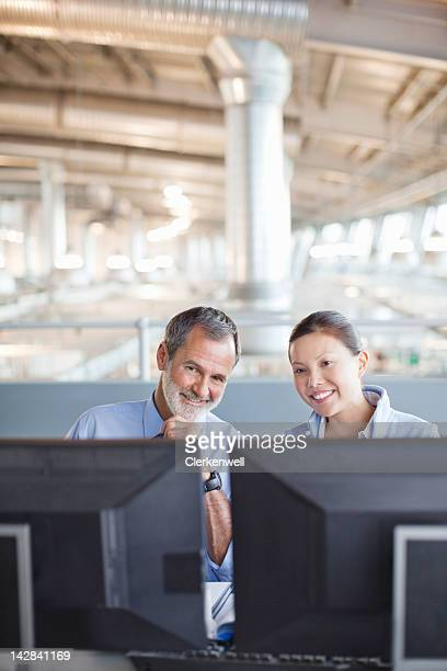 Businessman and businesswoman working at computers in factory