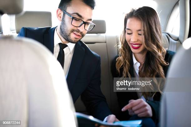 Businessman and businesswoman working in a car
