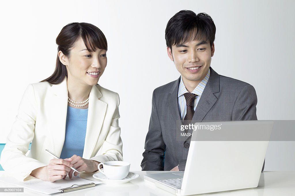 Businessman and Businesswoman Working on a Laptop : Stock Photo