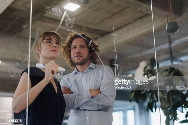 businessman and businesswoman working on a project in office - arbeitskollege stock-fotos und bilder
