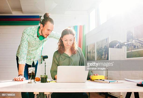 Businessman and businesswoman working on laptop in creative office