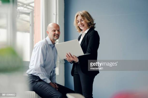 businessman and businesswoman working together on laptop - geschäftsleben stock-fotos und bilder