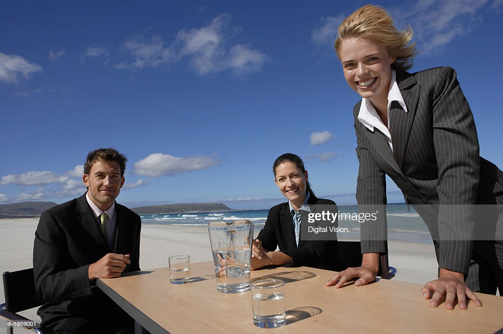 Businessman and Businesswomen Having a Meeting Outdoors on a Beach : Stock Photo