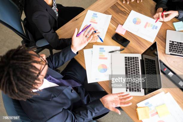 Businessman and businesswomen, in office meeting, using laptops, looking at data, overhead view