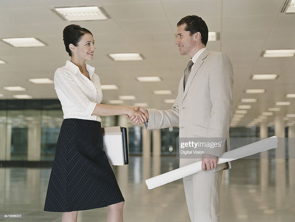 Businessman and Businesswomen Stand in an Empty Office Building Shaking Hands : Stock Photo