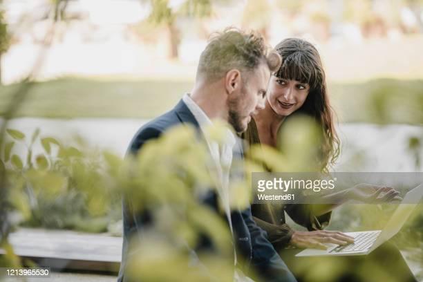 businessman and casual businesswoman using laptop outdoors - sitzbank stock-fotos und bilder