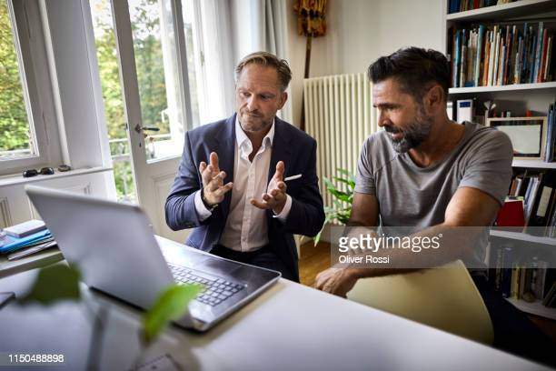 businessman and casual man sitting at desk with laptop - beratung stock-fotos und bilder