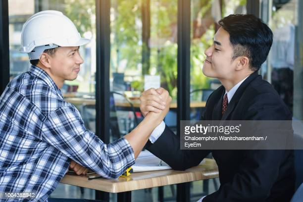 Businessman And Construction Worker Arm Wrestling On Table At Office