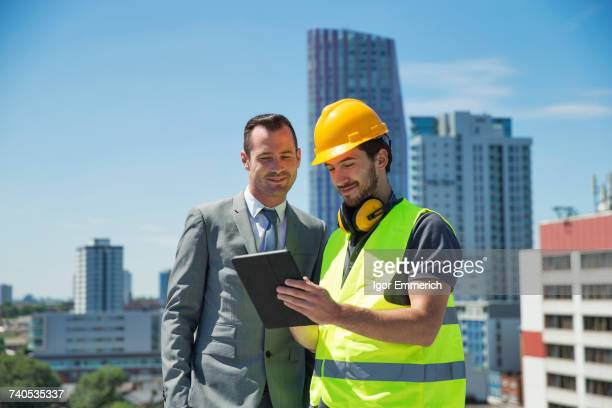 businessman and construction worker, outdoors, looking at digital tablet - real estate developer stock pictures, royalty-free photos & images
