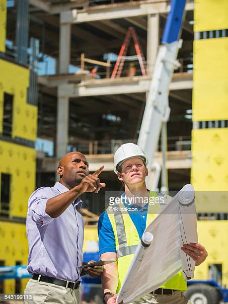 Businessman and construction worker reading blueprints at construction site