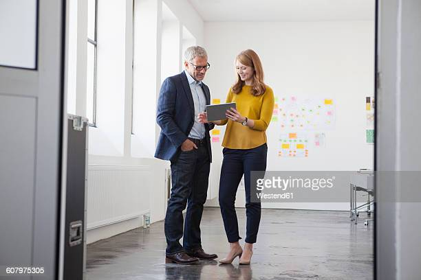 businessman and coworker discussing project in office - standing photos et images de collection