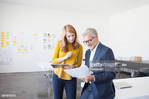 Businessman and coworker in office studying infographics