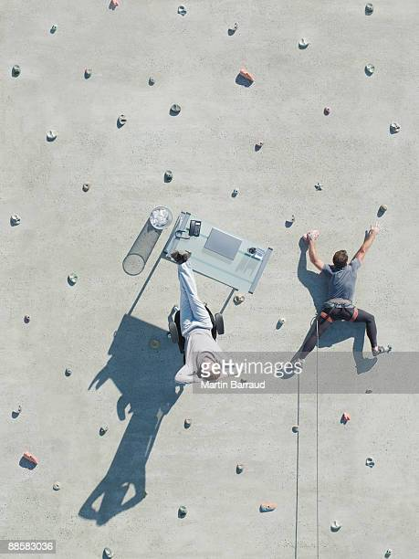 Businessman and desk on rock climbing wall
