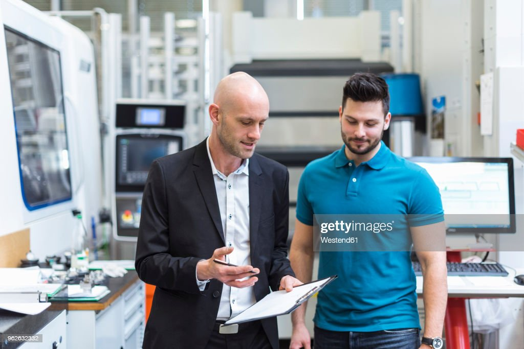 Businessman and employee discussing in modern factory : Stock Photo