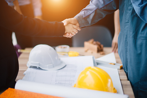 Businessman and engineer handshake closing a deal in construction site. Sucessful,engineering and business concept. 976560476