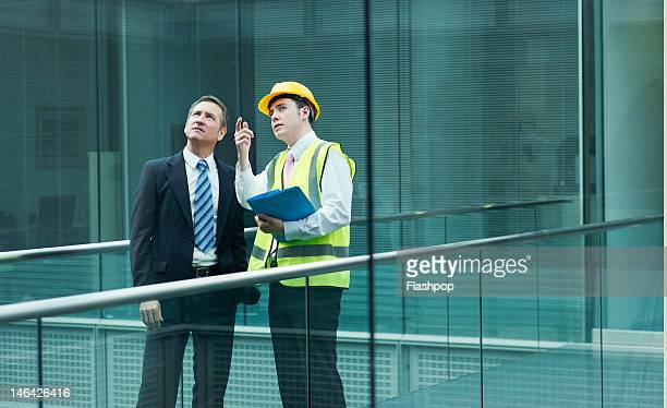 businessman and engineer in conversation - employee engagement stock pictures, royalty-free photos & images