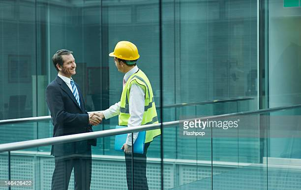 Businessman and engineer shaking hands