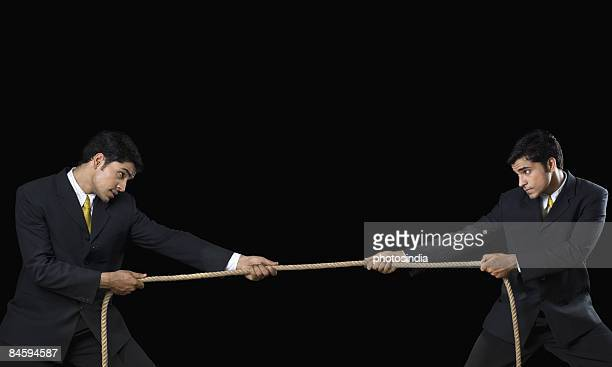 Businessman and his clone playing tug-of-war