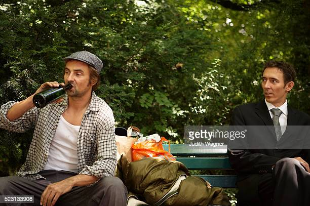 businessman and homeless man sitting on park bench - social inequality stock pictures, royalty-free photos & images