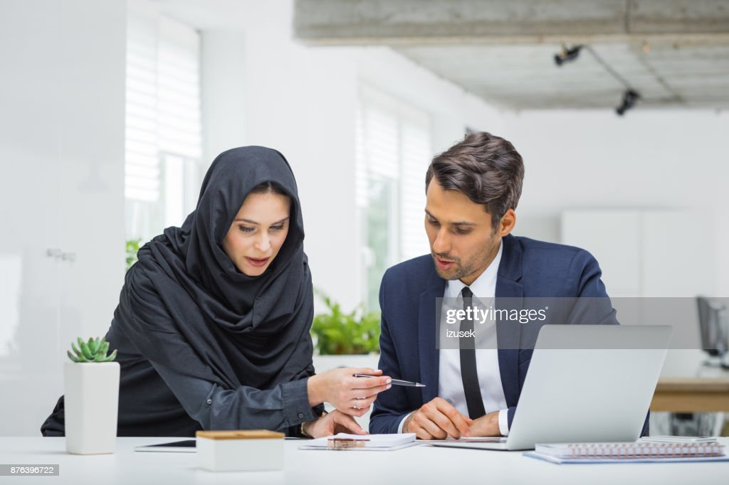Businessman and muslim businesswoman working on project : Stock Photo