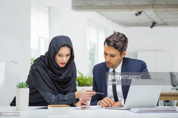 Businessman and muslim businesswoman working on project