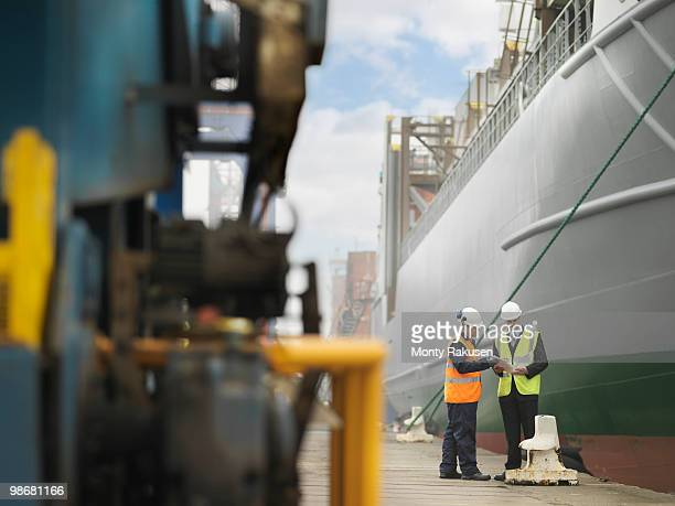 businessman and port worker with ship - monty rakusen stock photos and pictures