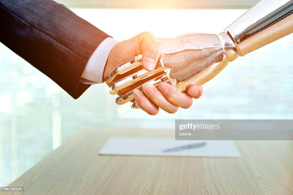 Geschäftsmann und Roboter schütteln im Innenbereich : Stock-Foto