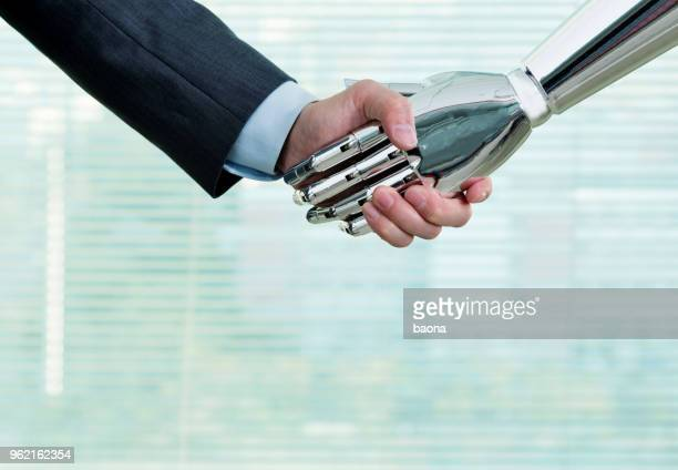 businessman and robot shaking indoors - human arm stock pictures, royalty-free photos & images