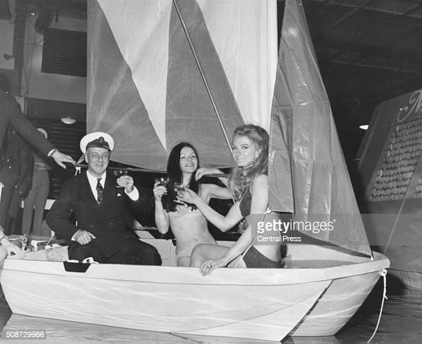 Businessman and sailor Sir Alec Rose posing with bikini clad women Tina Palmer and Miranda Rowe as they test the new fireproof bailing boat launched...