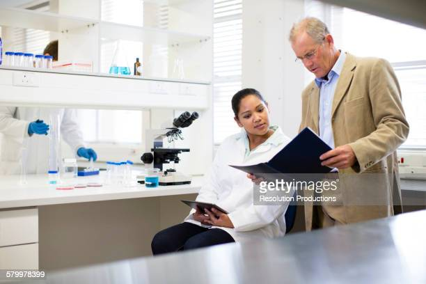 Businessman and scientist talking in laboratory