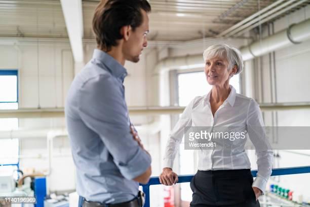 businessman and senior businesswoman talking in a factory - kontinuität stock-fotos und bilder