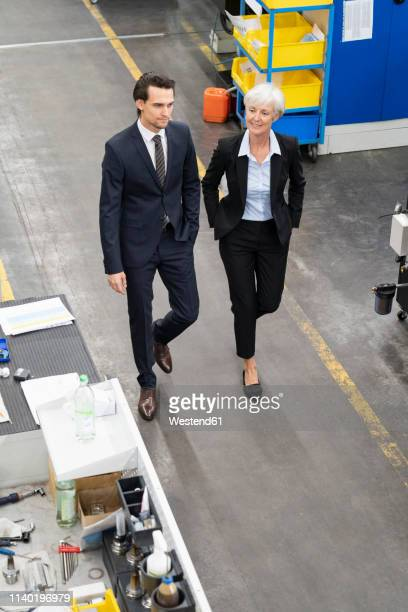 businessman and senior businesswoman walking in a factory - successor stock pictures, royalty-free photos & images