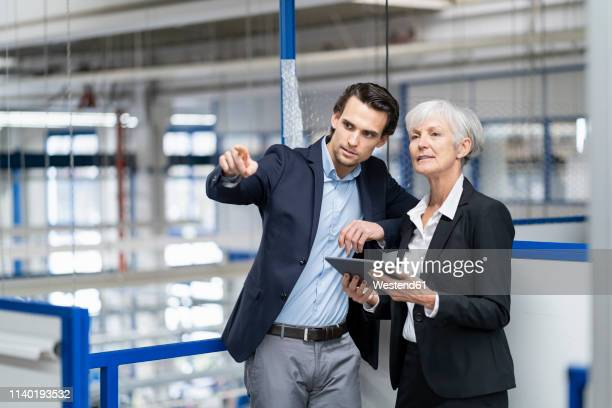 businessman and senior businesswoman with tablet talking in a factory - successor stock pictures, royalty-free photos & images