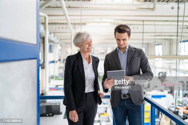 businessman and senior businesswoman with tablet talking in a factory - 後任 ストックフォトと画像