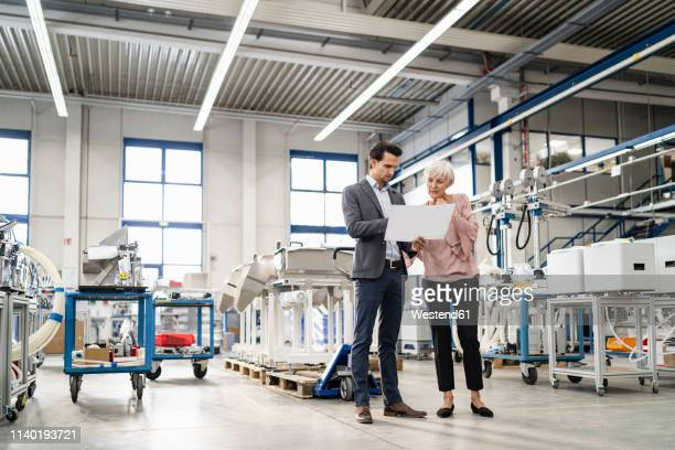 businessman and senior woman looking at plan in a factory - businesswear stock pictures, royalty-free photos & images