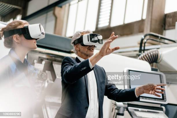 businessman and skilled worker in high tech enterprise, using vr glasses - simulatore di realtà virtuale foto e immagini stock