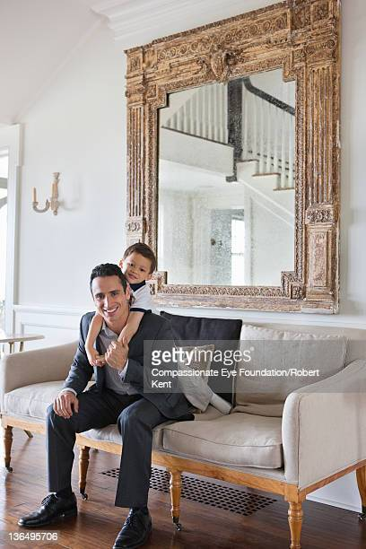 Businessman and son on sofa in living room