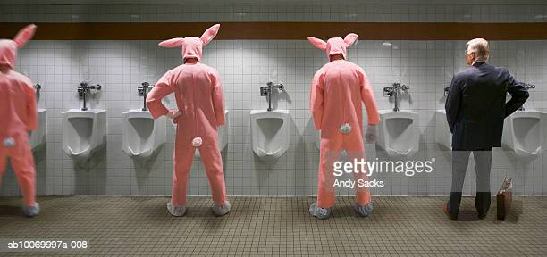 businessman and three men wearing rabbit costume standing at urinal, rear view (digital composite) - chelsea mask stock pictures, royalty-free photos & images