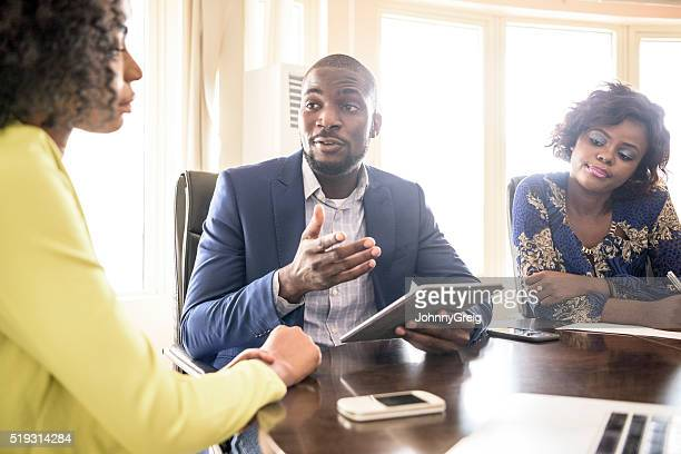 businessman and two female colleagues in meeting - nigeria stock pictures, royalty-free photos & images