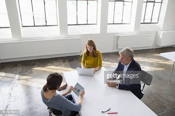 Businessman and two women in conference room using portable devices