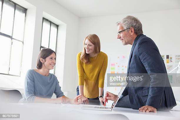Businessman and two women in office having a meeting