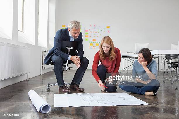 Businessman and two women in office looking at construction plan