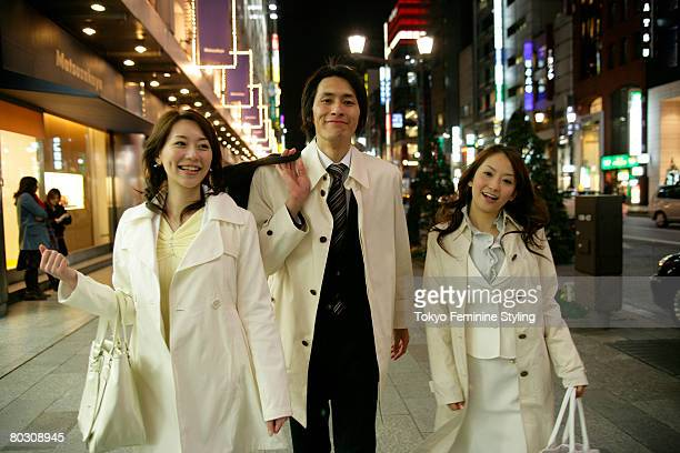 Businessman and two women walking on the street at night