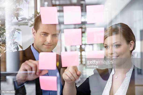 Businessman and woman arranging post it notes on office window