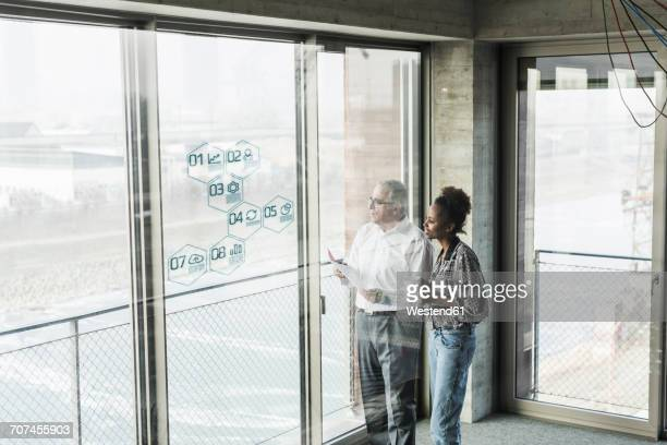 Businessman and woman at windowpane with data in office