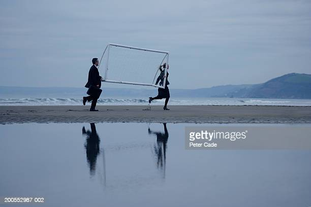 Businessman and woman carrying goal post by beach