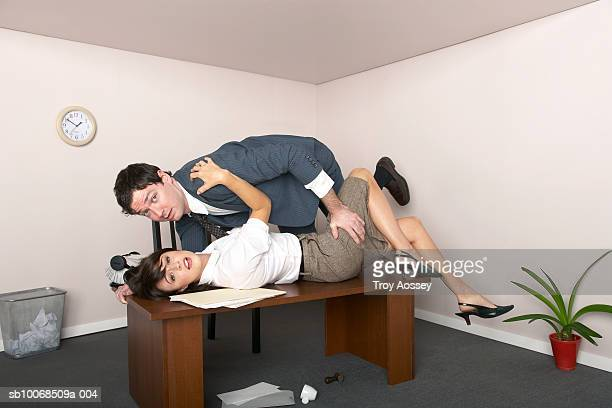 businessman and woman embracing on top of desk in office, portrait, side view - work romance stock pictures, royalty-free photos & images