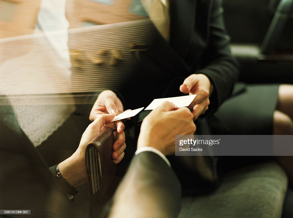 Businessman and woman exchanging business cards, close up : Stock Photo